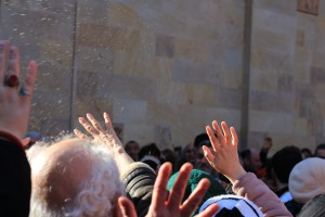 GM people reaching out to receive the blessings of the holy water.